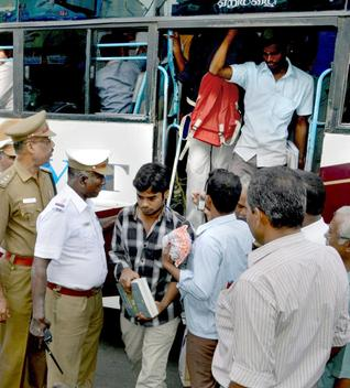 Police personnel warning footboard travellers in a private bus at Hasthampatti Roundtana in Salem