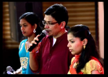 Edwin Figarez, priest singing with girls
